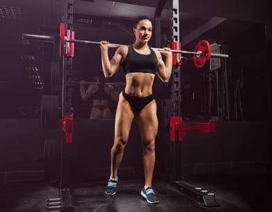 woman squats on power cage